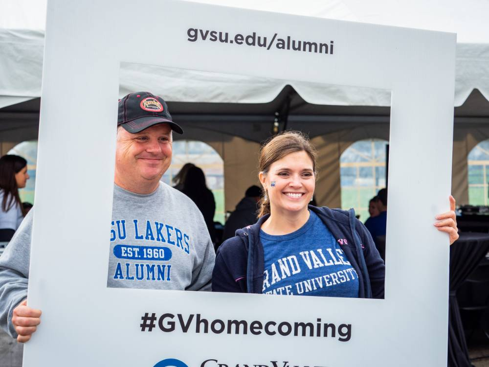 2 Alumni pose with the #GVhomecoming sign