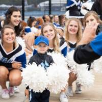 Little Laker poses with Laker Cheerleaders