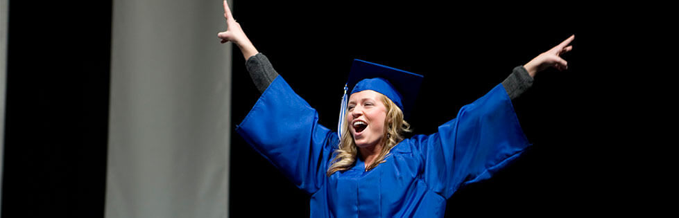 Female student with arms raised at commencement