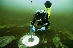 NOAA diver taking a water sample with syringe from a benthic metabolism chamber