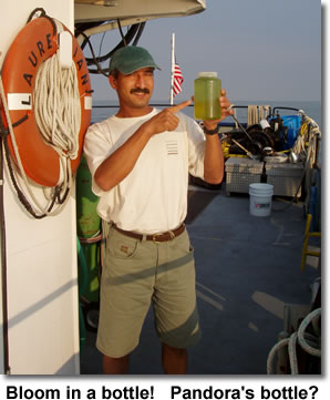 Dr. Bopi Biddanda holds a bottle with water from an algal bloom in Lake Erie in 2003