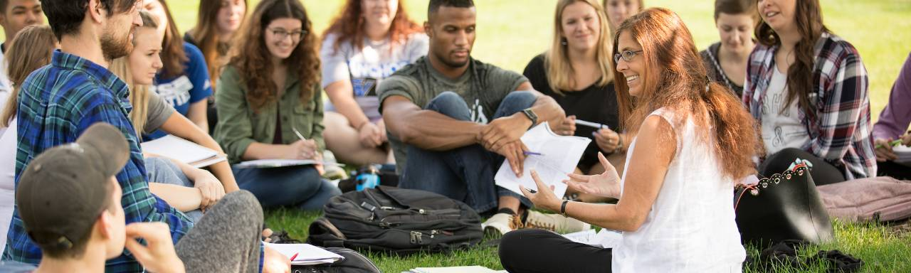 Dr. Val Peterson sitting on the lawn with students for class, smiling.