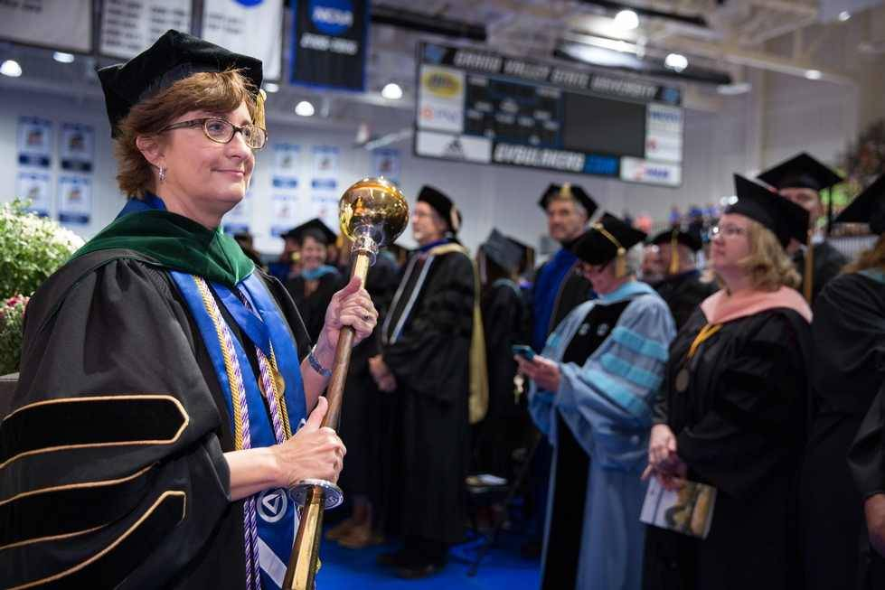 A woman holds the mace at a convocation ceremony