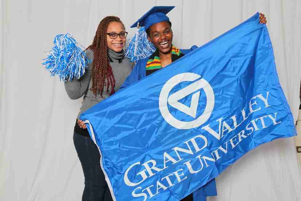 Two GVSU graduates hold a blue GVSU flag