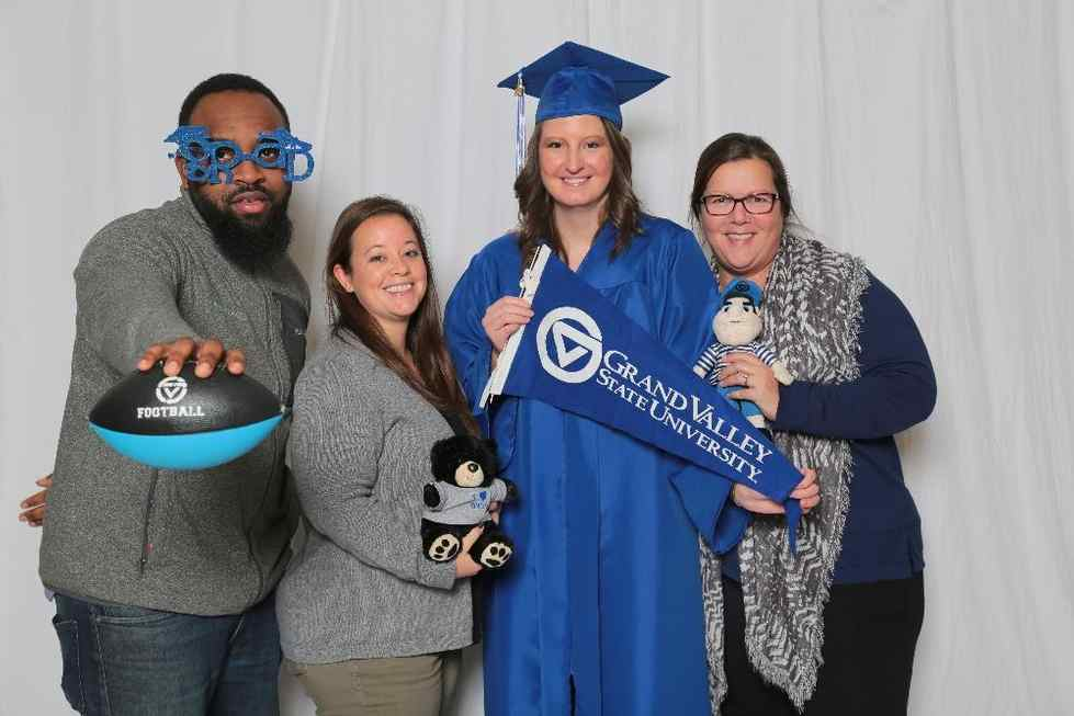 Four people holding GVSU gear with a GVSU graduate