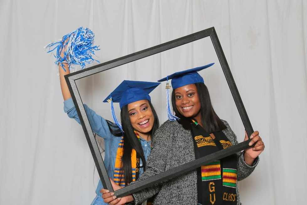 Two GVSU graduates standing behind an empty picture frame