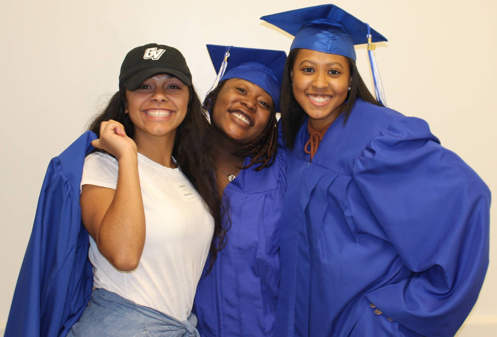 Three students smiling proudly wearing their blue Grand Valley graduation cap and gowns.