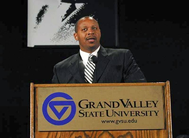 Oliver Wilson standing behind a Grand Valley State University podium giving a speech