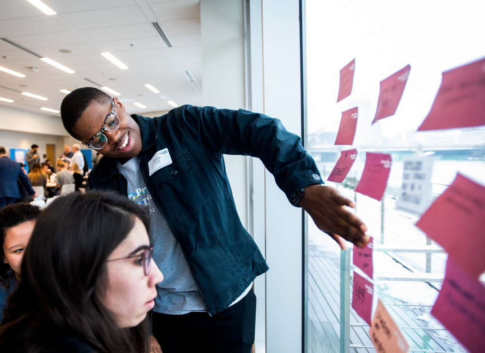 Students add sticky notes to a window during a design thinking workshop