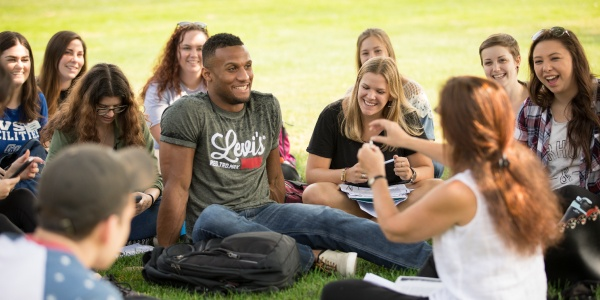 Students sitting together in the grass on campus.
