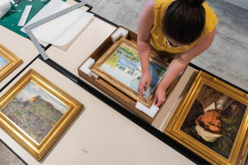 A person packages paintings for exhibit