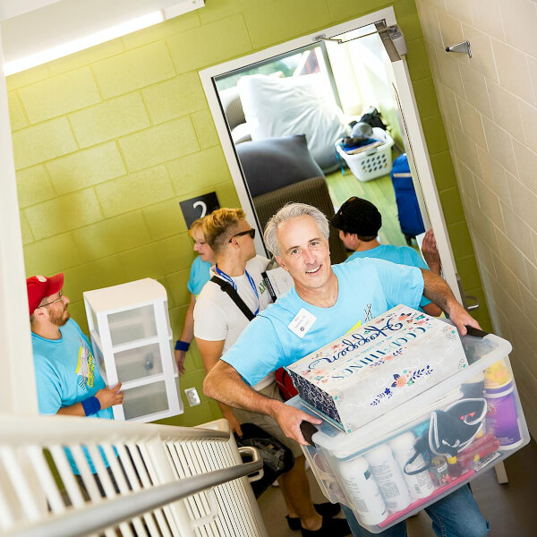 Dan Hartlieb joins other alumni to help first-year students move into their living centers.