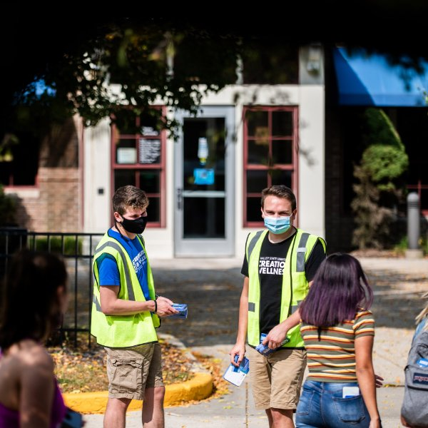 Two male GVSU students in yellow vests give another GVSU student a reusable face covering on the Allendale Campus.