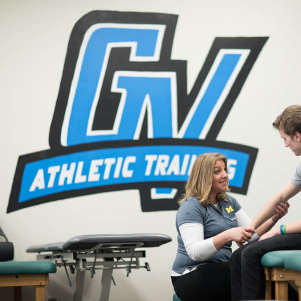 A photo of an athletic trainer working with a student.