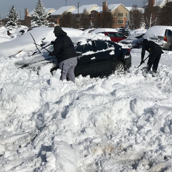 Members of GVPD help students on the Allendale Campus remove snow from their cars.