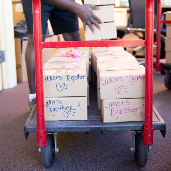 Care packages are loaded on a cart, Lakers Together drawn on packages