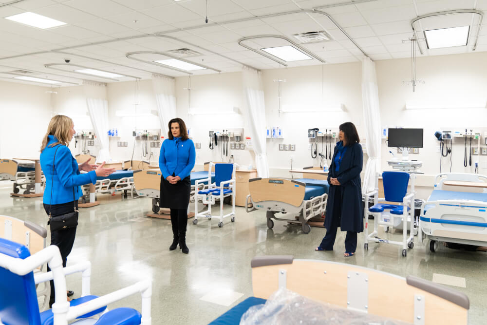 three women standing in a lab; including governor, President Mantella and Spectrum Health CEO