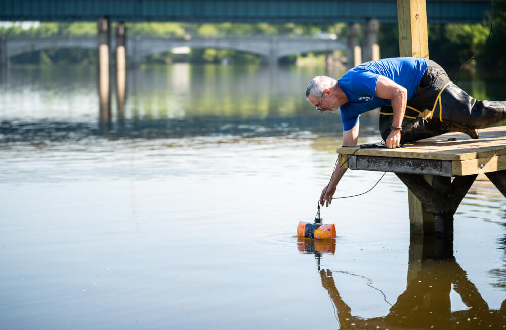 Peter Wampler, professor of geology, collects a sample from the Grand River.