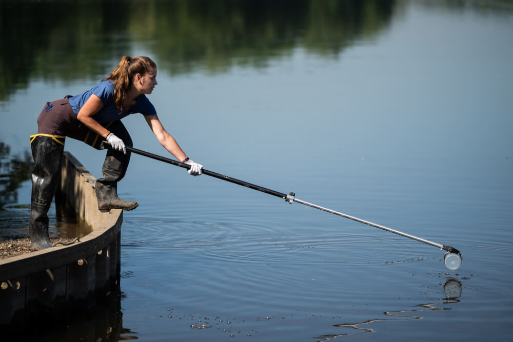 Jillian Ashton collects a sample from the Grand River.