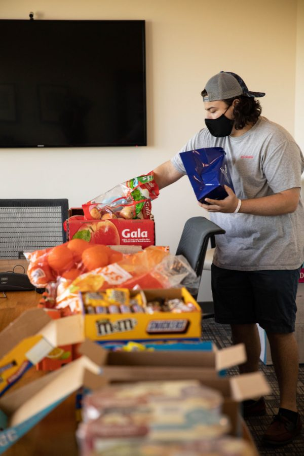 A student wearing a mask fills care packages in an office.