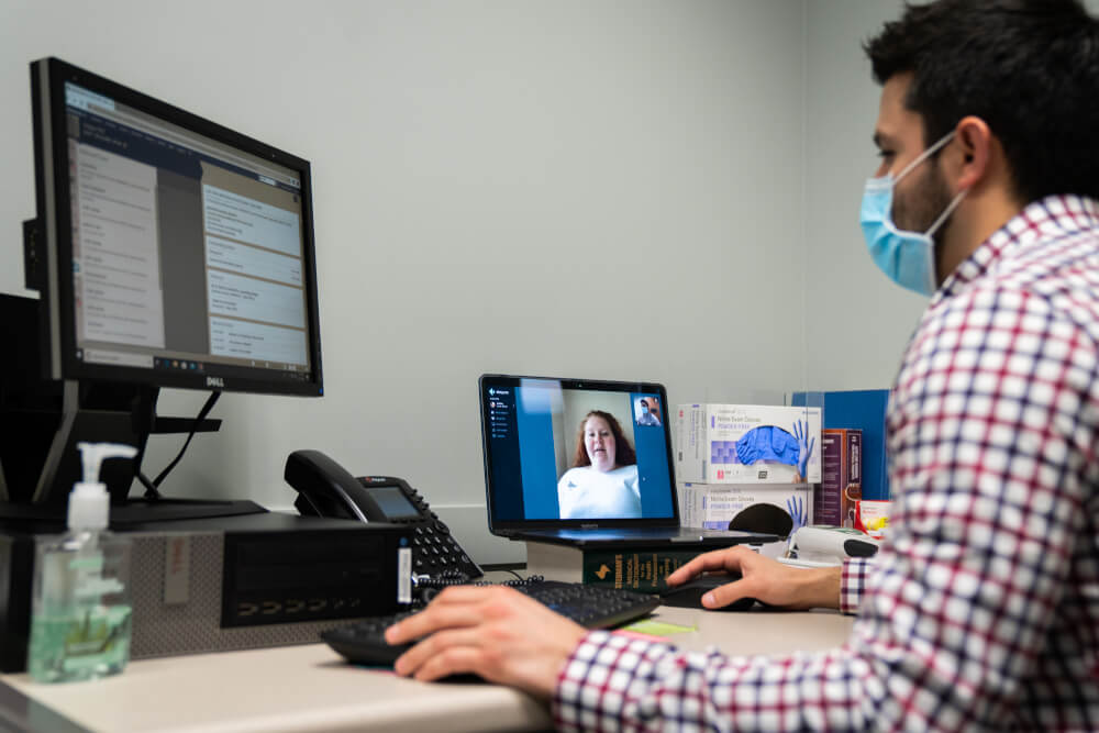 man wearing medical mask sitting at computer conducting a zoom-like meeting with a womam