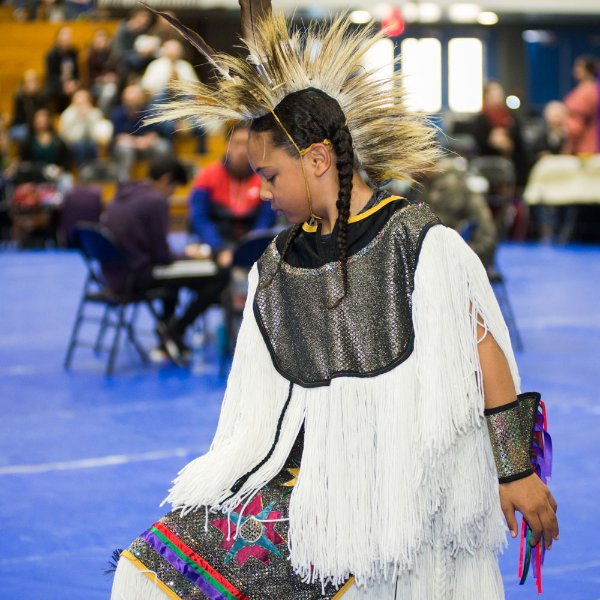 participant in a GVSU pow wow, wearing white native regalia