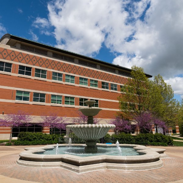 Padnos Hall photo with blue sky, clouds and fountain