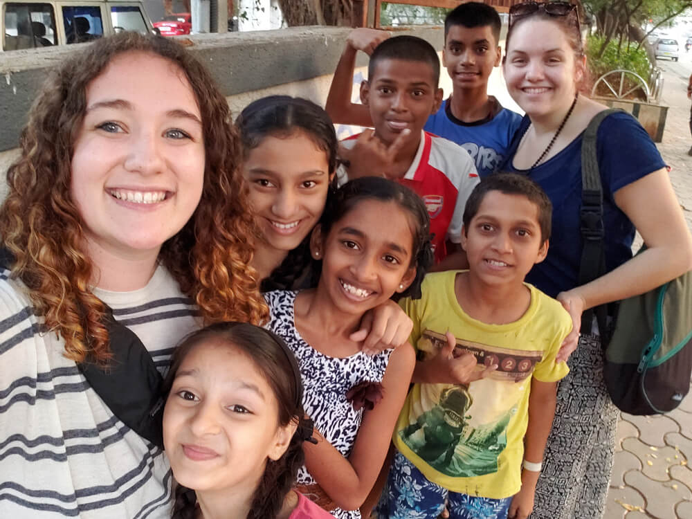 young woman takes selfie with group of students in India