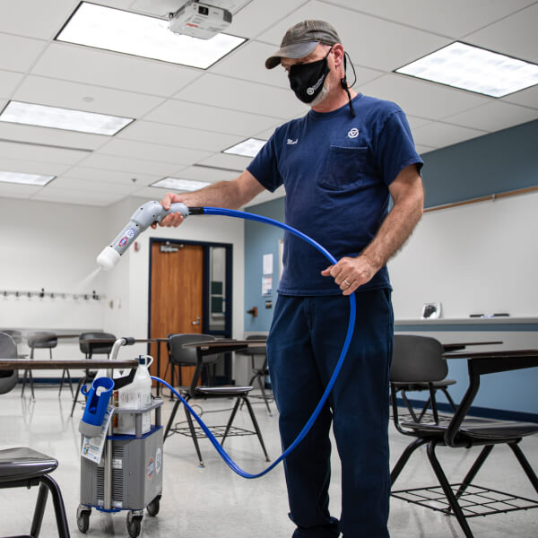 Photo of employee cleaning a classroom.