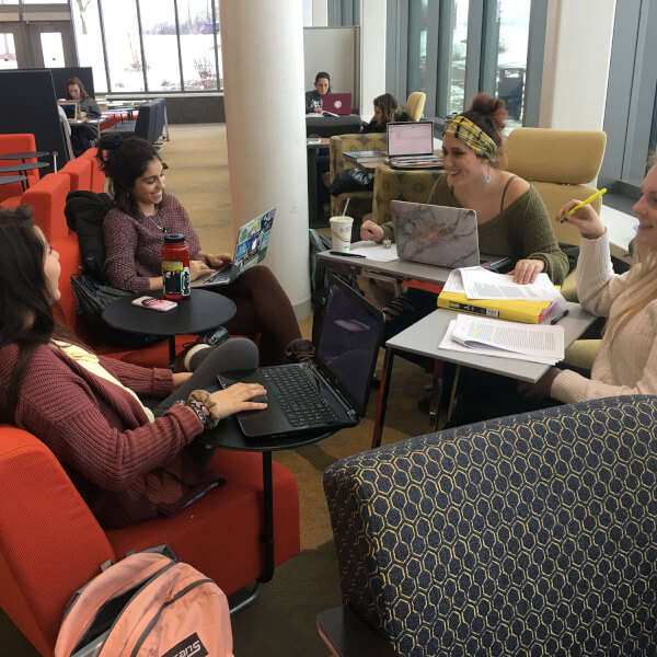four students in chairs, with computers, papers