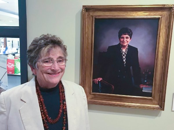 Johnine Callahan, retired professor and honors college director, stands next to her portrait in Niemeyer Living Center at the 10th anniversary of the honors college.