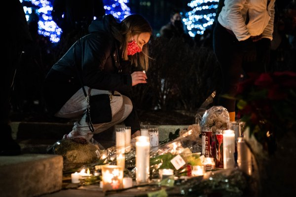 A person places a candle amongst other candles and flowers during a December 16 vigil on GVSU's Allendale Campus.