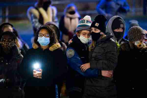 People hug during a December 16 candlelight vigil on GVSU's Allendale Campus held in memory of first-year student Taylor DeRosa.