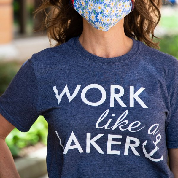 "A woman wearing a blue ""Work like a Laker"" t-shirt and face covering."