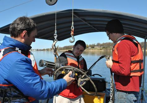 From left, Observatory Manager Scott Kendall, graduate student Leon Gereaux, and Research Technician Tom Holcomb adjust settings as they lower a string of sensors into the lake.