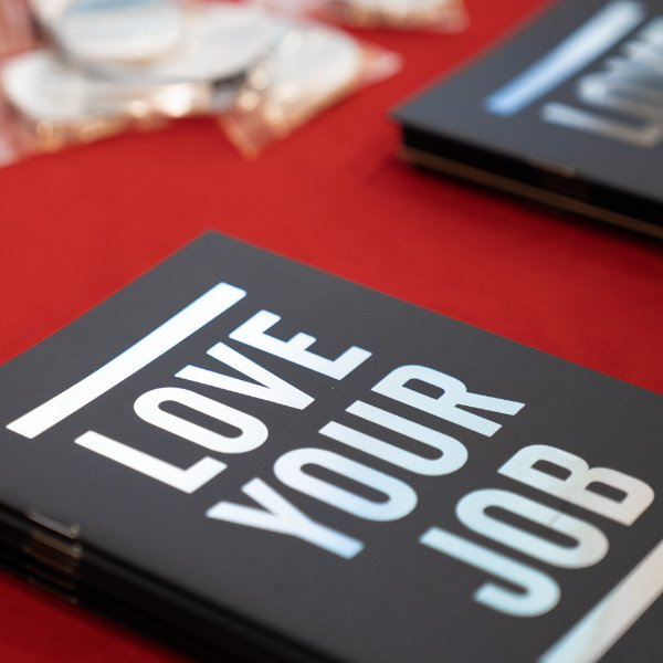 "A notebook on a table that reads ""Love Your Job"""