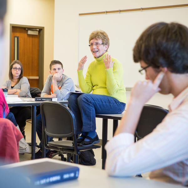 woman sitting on desk, talking with students in class