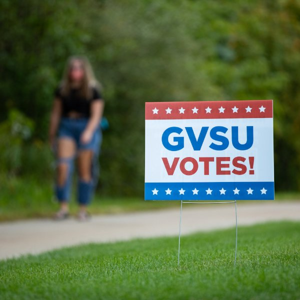 A red, white and blue sign that reads: GVSU Votes! with stars