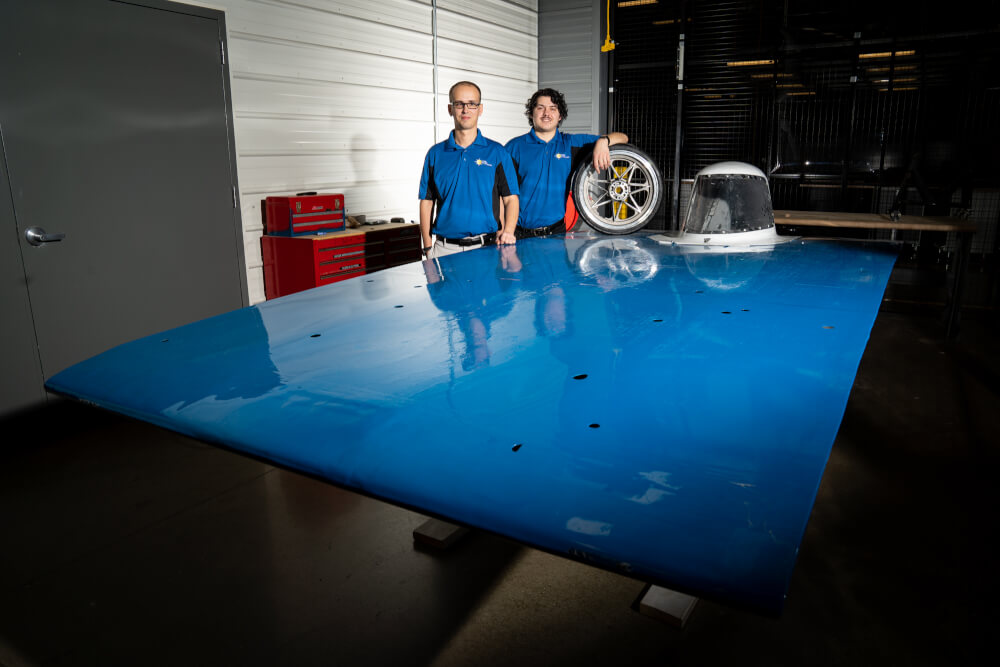 Ryan Aldridge, left, operations manager at the Innovation Design Center, and Adam Duke, president of the GVSU Solar Racing Team, are pictured with the GVSU solar-powered race car.