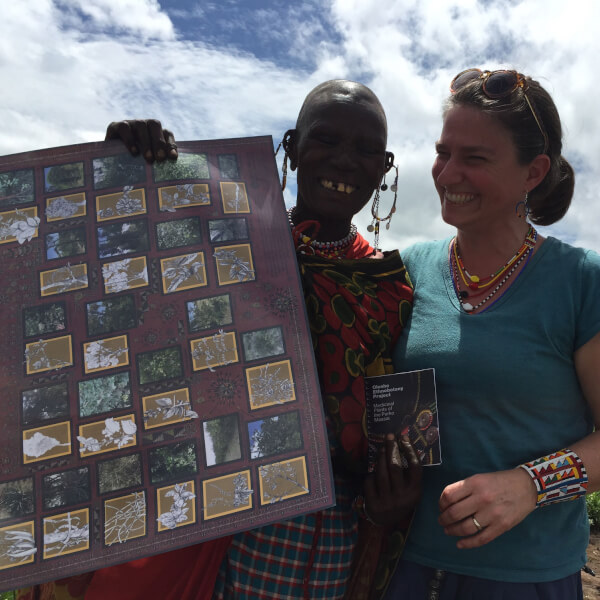 Kristin Hedges (right) pictured delivering her catalog to local healers in the Maasai community.