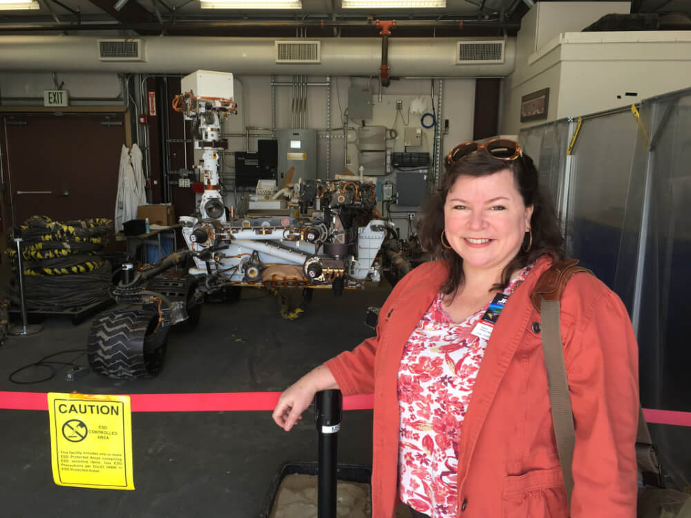 Deana Weibel stands with a copy of the Mars Curiosity rover, used for testing.