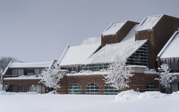 winter photo of Kirkhof Center with snow on ground and roof, ice