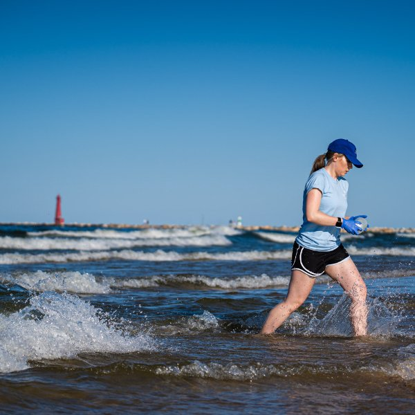 Lexy Porter takes a water sample from Lake Michigan at Pere Marquette Beach in Muskegon.