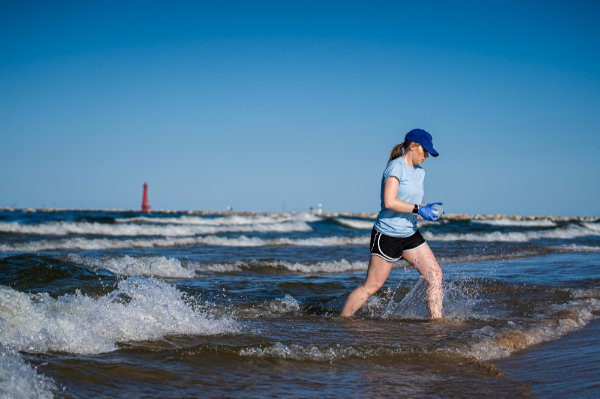 Lexy Porter takes a water sample from Lake Michigan in Muskegon.