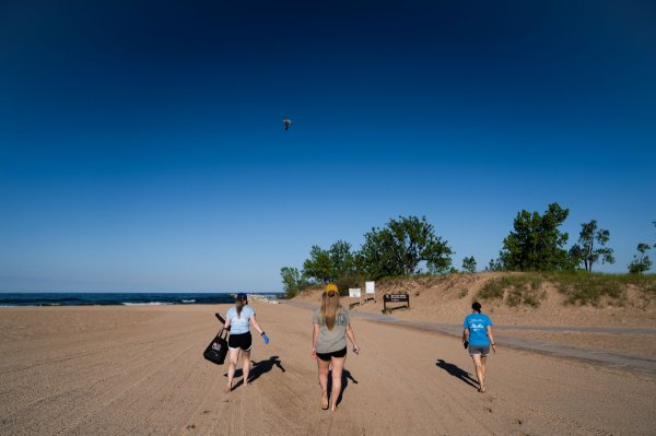 Lexy Porter, Maggie Brenneman and Molly Lane (left to right) walk down Pere Marquette Beach in Muskegon.