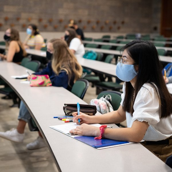 Students are pictured in class, taking notes and wearing masks