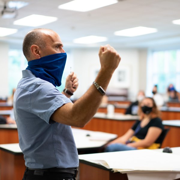 With a face covering, Kurt Ellenberger, professor of music, Meijer Honors College, stands in front of students in the Niemeyer Learning and Living Center.