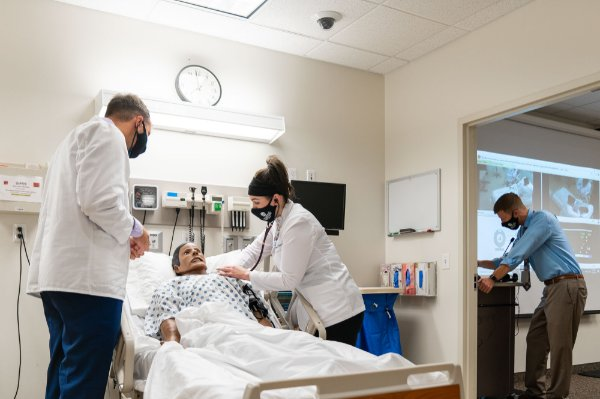 Students majoring in physician assistant studies practice their clinical skills in the Simulation Lab in in the Cook-DeVos Center for Health Sciences. Andrew Booth, associate professor of physician assistant studies, is at far right.