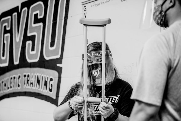 Wearing a face shield, Maylee Bowers does a crutch fitting during her principles of athletic training lab on the first day of classes.