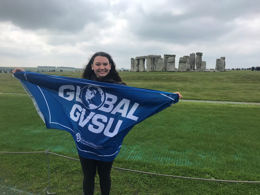 Ashley Brown holds a GVSU study abroad flag in front of Stonehenge.